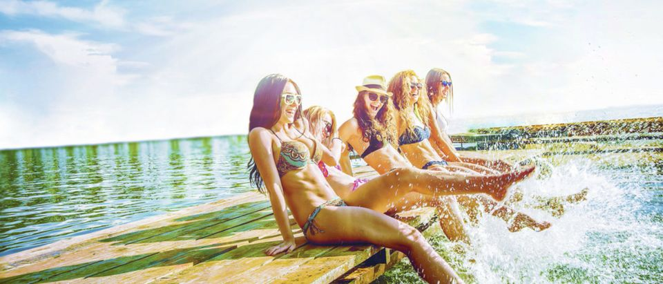 A group of happy, young women splash their feet in the water (Shutterstock/maradon 333)
