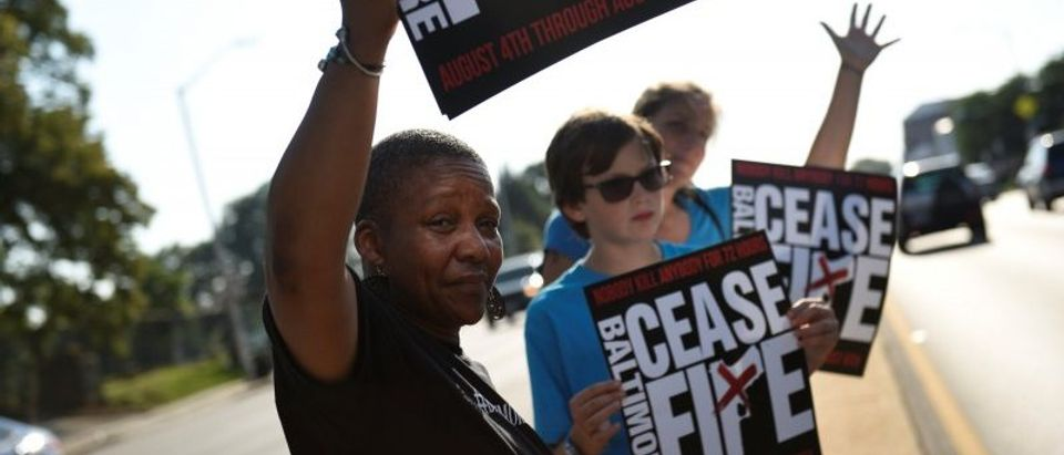 """People hold signs at the """"Stop the Violence"""" rally at the intersection of Edmondson Avenue and Wildwood Parkway in Baltimore"""