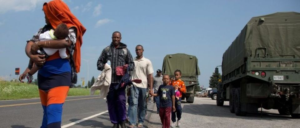 A group of asylum seekers walk down the street as they are escorted from their tent encampment to be processed at Canada Border Services in Lacolle, Quebec Canada