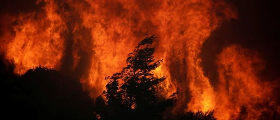 Flames rise as a wildfire burns near the village of Varnavas