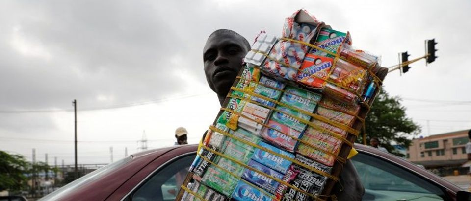 A man selling sweets in traffic holds Nigerian naira along a road near a currency exchange market in Ikeja district in Lagos