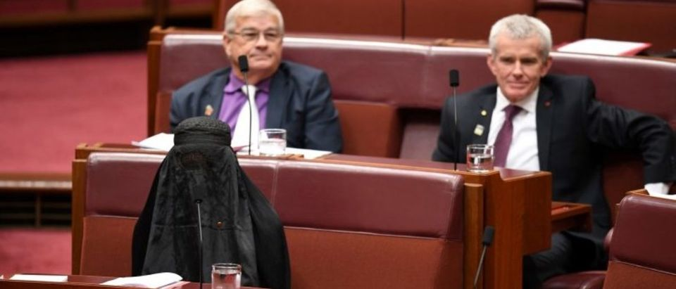 Australian One Nation party leader, Senator Pauline Hanson (L) wears a burqa in the Senate chamber at Parliament House in Canberra