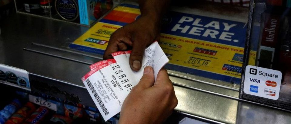 A customer purchases Powerball lottery tickets for a $700 million jackpot at a newsstand in New York
