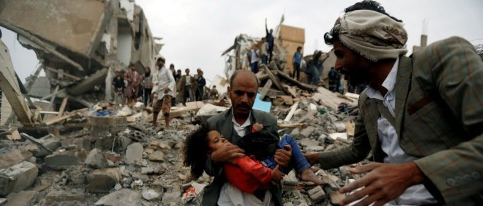 Man carries an injured girl rescued from the site of a Saudi-led air strike in Sanaa