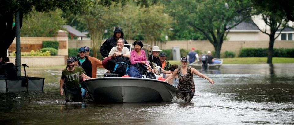 People evacuate by boat from the Hurricane Harvey floodwaters in Houston