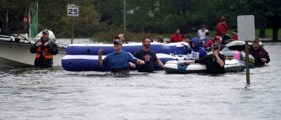 People are evacuated by volunteers in waist-deep floodwaters from Hurricane Harvey in Houston