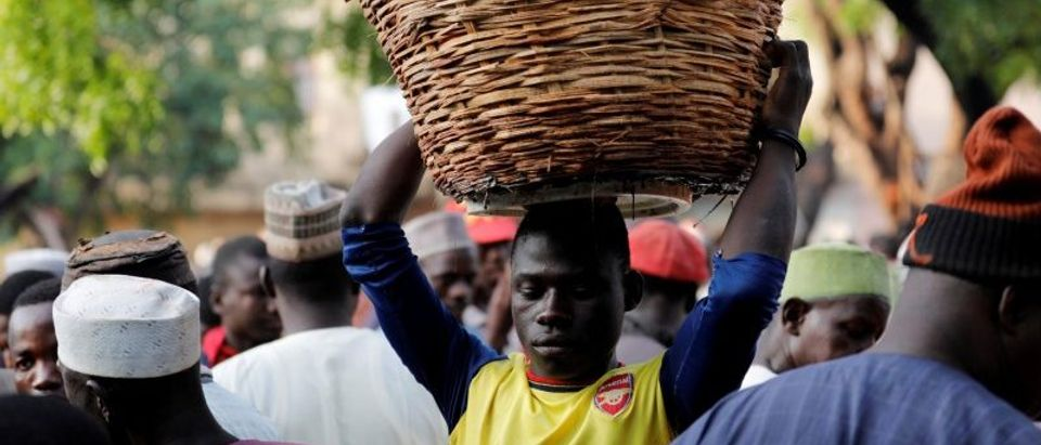 A labourer carries a basket of tomatoes through the Yankaba market in Kano