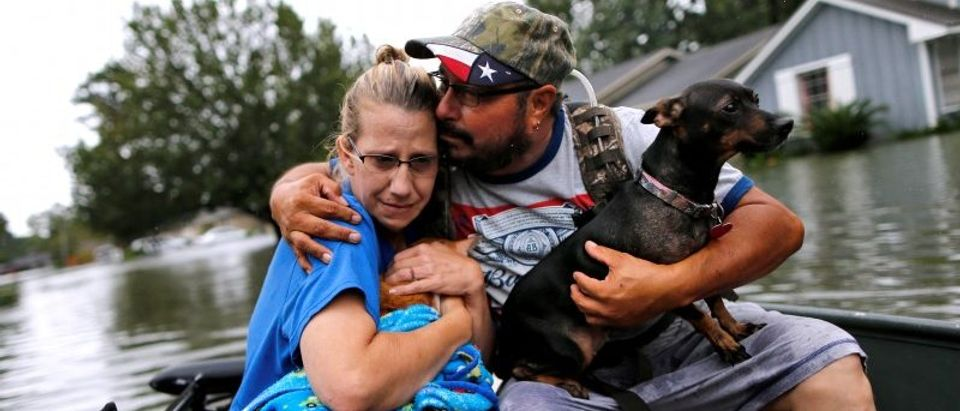 David Gonzalez comforts his wife Kathy after being rescued from their home flooded by Tropical Storm Harvey in Orange, Texas