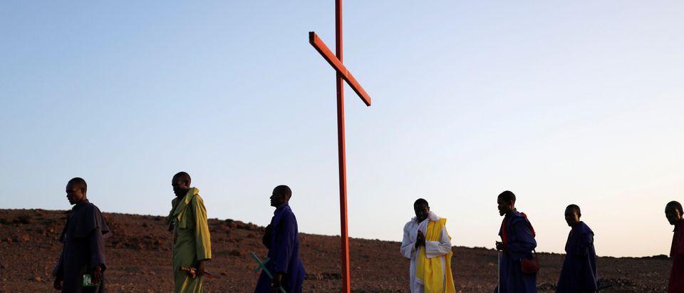 Men pray outside a Legio Maria African Mission Church in Loiyangalani
