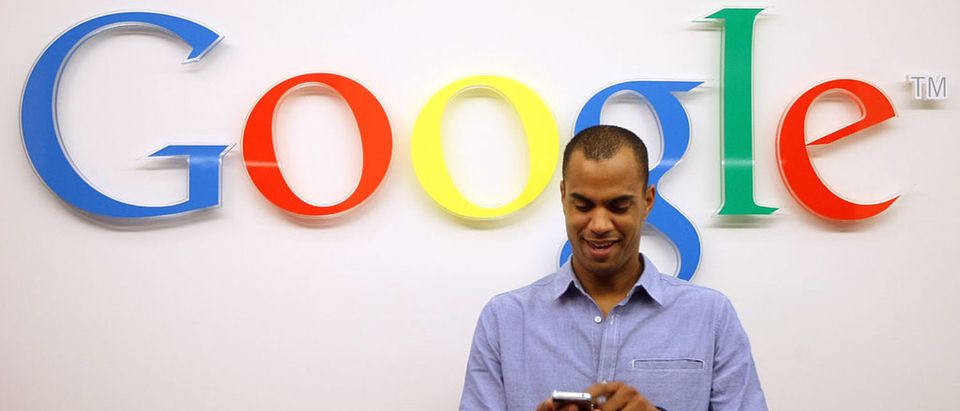 BERLIN, GERMANY - SEPTEMBER 26: A visitor uses a cell phone in front of the Google logo on September 26, 2012 at the official opening party of the Google offices in Berlin, Germany. Although the American company holds 95% of the German search engine market share and already has offices in Hamburg and Munich, its new offices on the prestigious Unter den Linden avenue are its first in the German capital. (Photo by Adam Berry/Getty Images)