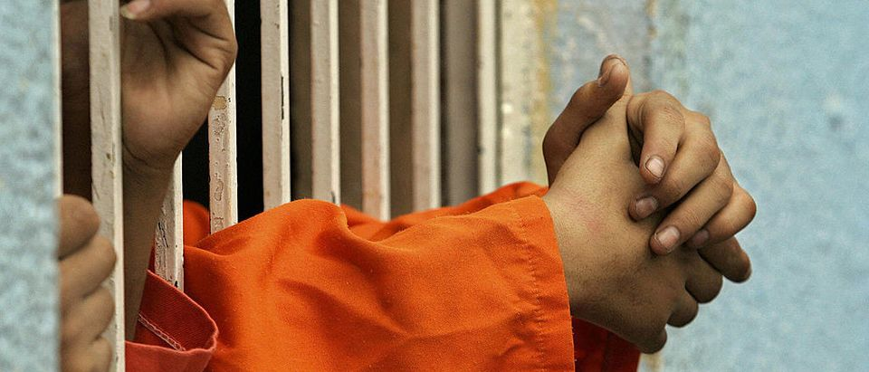 An Inmate stretches his hands through prison bars. (Getty Images, JOELLE BASSOUL)