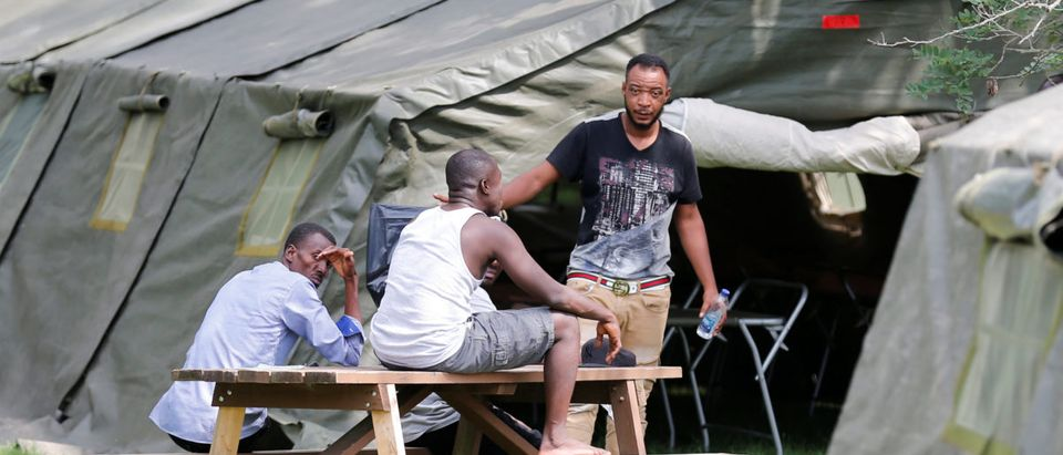 Refugees sit outside one of the tents set up to house the influx of asylum seekers by the Canadian Armed Forces near the border in Lacolle
