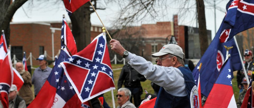 Supporters salute the Confederate flag during a rally held by Sons of Confederate Veterans in Shawnee