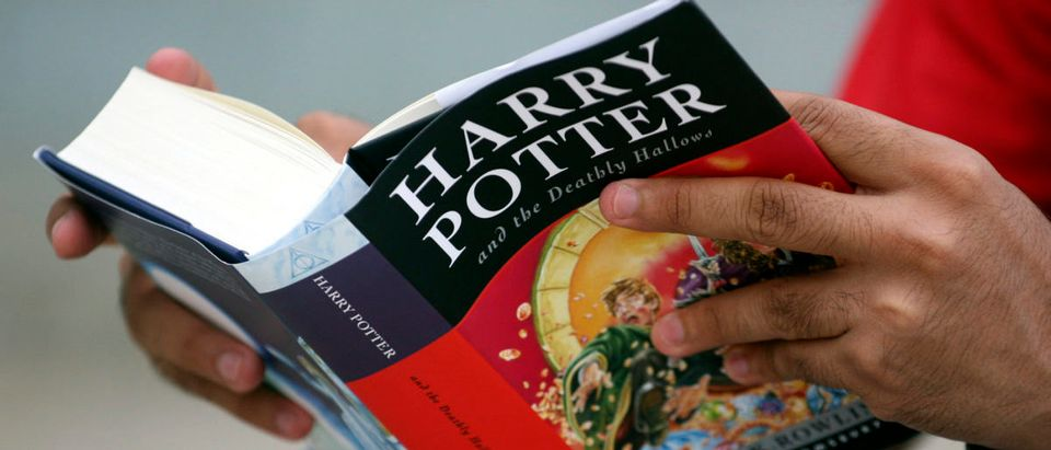 """A fan reads the new """"Harry Potter and the Deathly Hallows"""" outside a bookstore in Ahmedabad"""