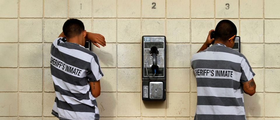 Inmates serving a jail sentence make a phone call at Maricopa County's Tent City jail in Phoenix
