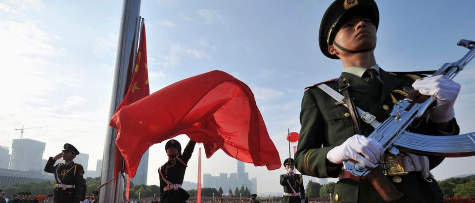 A paramilitary policeman unfurls a Chinese national flag during a flag-raising ceremony to mark the 65th anniversary of the founding of the People's Republic of China, in Hefei