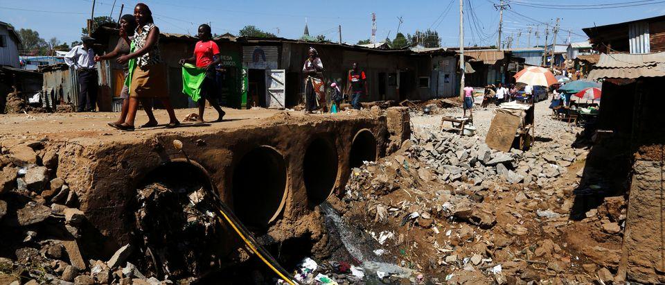 People walk near open sewers in the Kibera slum of Kenya's capital Nairobi February 26, 2015. REUTERS/Darrin Zammit Lupi (KENYA - Tags: SOCIETY) - RTR4RC2E