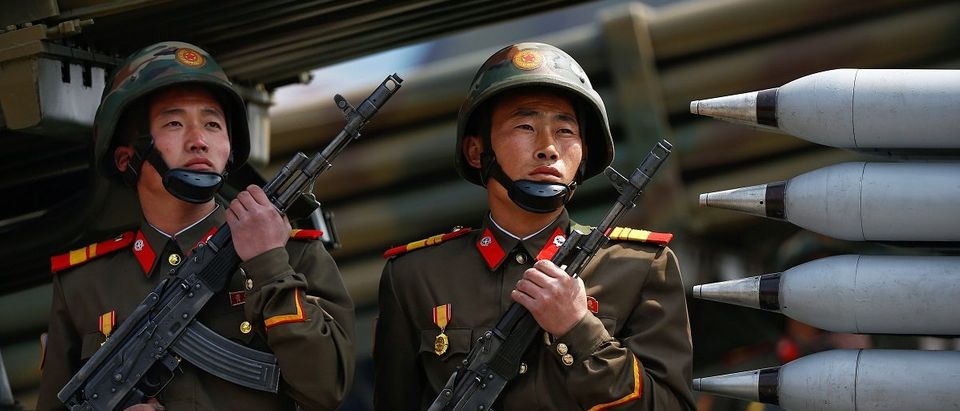 Soldiers hold weapons while sitting on a vehicle carrying rockets as it drives past the stand with North Korean leader Kim Jong Un during a military parade marking the 105th birth anniversary of country's founding father, Kim Il Sung in Pyongyang