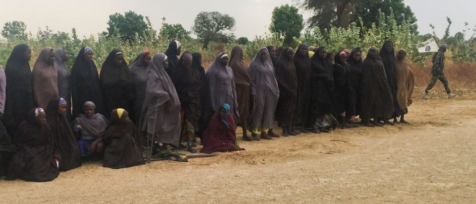 A man carrying a Boko Haram flag walks past a group of 82 Chibok girls as the girls wait to be released in exchange for several militant commanders, near Kumshe