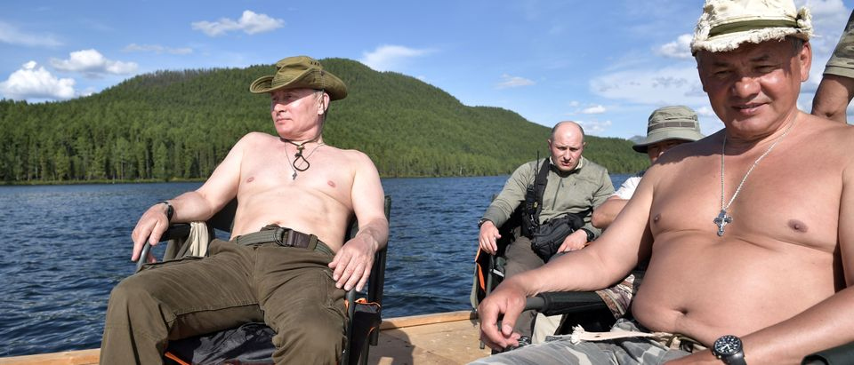 Reuters/ Russian President Vladimir Putin and Defence Minister Sergei Shoigu rest during the hunting and fishing trip which took place on August 1-3 in the republic of Tyva in southern Siberia