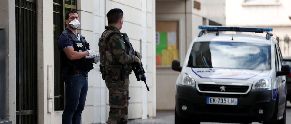 A police investigator and an armed soldier work near the scene where French soliders were hit and injured by a vehicle in the western Paris suburb of Levallois-Perret