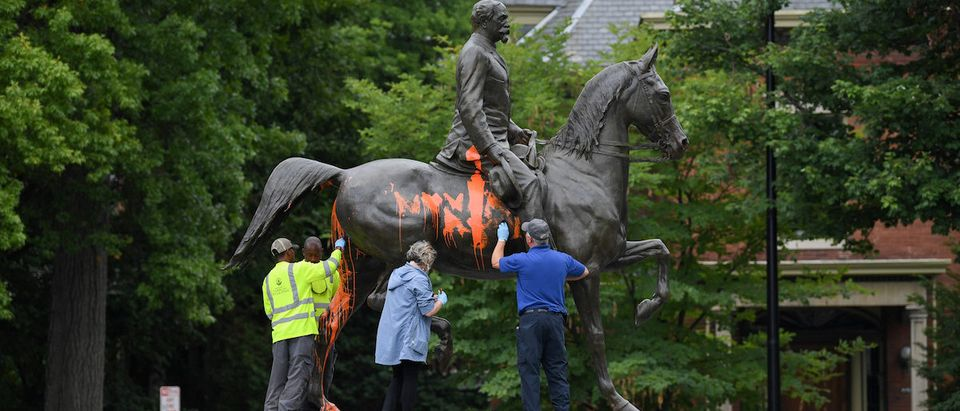 Municipal workers attempt to remove paint from a monument dedicated to Confederate soldier John B. Castleman that was vandalized late Saturday night in Louisville