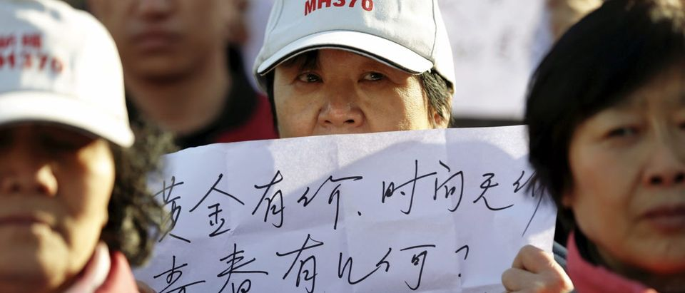 Family members of passengers onboard Malaysia Airlines flight MH370 which went missing in 2014 hold messages in front of reporters during their gathering near the Malaysian Embassy on the second anniversary of the disappearance of MH370, in Beijing