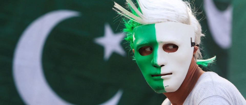 A vendor wears a mask with the colours of the Pakistani flag as people prepare to celebrate the country's Independence Day on August 14 at a roadside stall in Islamabad