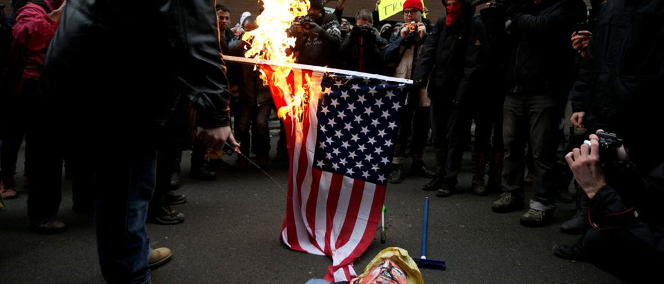 Protesters burn the American flag and an effigy of U.S. President Donald Trump in front of the U.S. embassy in Montreal