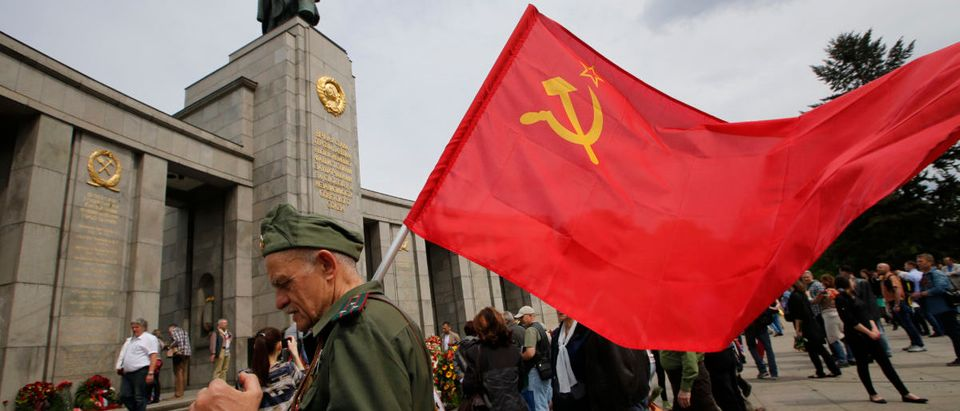 A man waering a Red Army uniform holds a Soviet flag during celebrations to mark Victory Day at the Soviet War Memorial near the Reichstag building, in Tiergarten district of Berlin