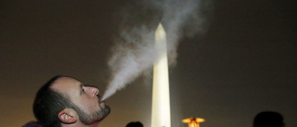 "Participant Ian Kreer exhales from an e-cigarette in front of the Washington Monument during a 48-hour vigil called ""Catharsis on the Mall: A Vigil for Healing the Drug War"" on the U.S. National Mall in Washington November 21, 2015. Participants burned an interactive art piece called the Temple of Essence dedicated to ""victims of the war on drugs."" REUTERS/Jim Bourg"