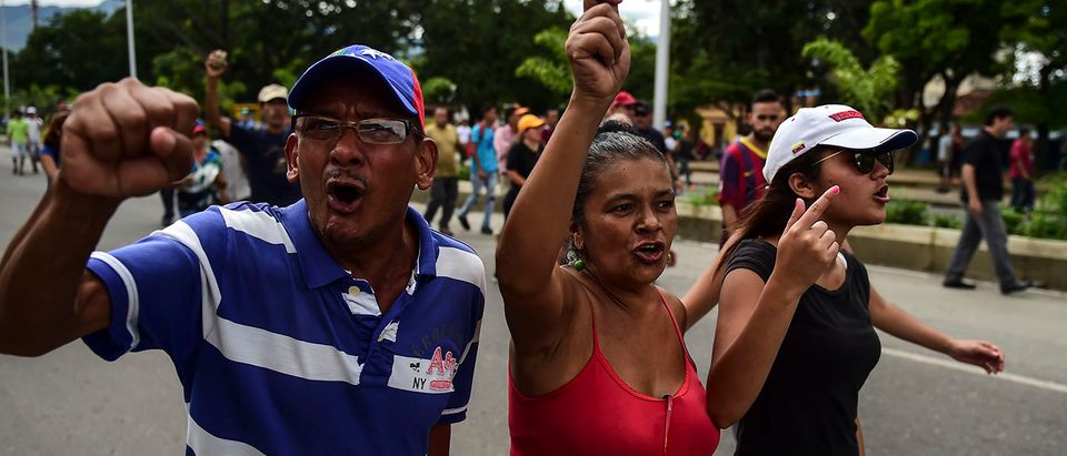 """Anti-government activists protest in Venezuela's third city, Valencia, on August 6, 2017, a day after a new assembly with supreme powers and loyal to President Nicolas Maduro started functioning in the country. In the video posted online earlier, allegedly at an army base used by the National Bolivarian Armed Forces in Valencia, a man presenting himself as an army captain declared a """"legitimate rebellion... to reject the murderous tyranny of Nicolas Maduro"""" and demanded a transitional government and """"free elections."""" After the video surfaced, military chiefs said troops had put down the """"terrorist"""" attack. PHOTO: Getty Images/Ronaldo SCHEMIDT"""