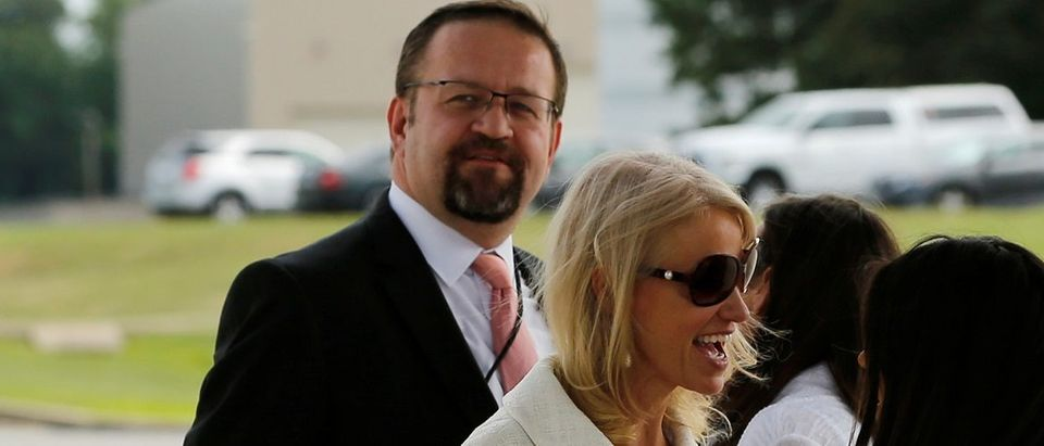 White House adviser Sebastian Gorka (L), standing with White House counselor Kellyanne Conway (C), waits for U.S. President Donald Trump to arrive to board Air Force One for travel to Ohio from Joint Base Andrews, Maryland, U.S. July 25, 2017. Picture taken July 25, 2017. REUTERS/Jonathan Ernst.
