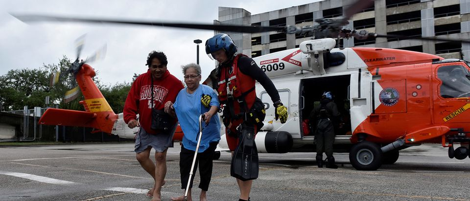 Evacuees Rickey Manuel and Marjory Manuel exit a U.S. Coast Guard helicopter that rescued them after Hurricane Harvey inundated the Texas Gulf coast with rain and flooded their home