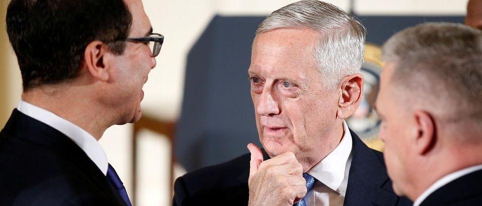U.S. Secretary of Defense Mattis speaks with U.S. Secretary of the Treasury Mnuchin at the White House in Washington