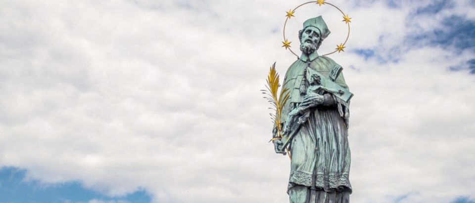 An old baroque statue of St John Of Nepomuk (Nepomucene) on the Charles' bridge in Prague, with cloudy sky (Thoom/shutterstock_343464764)