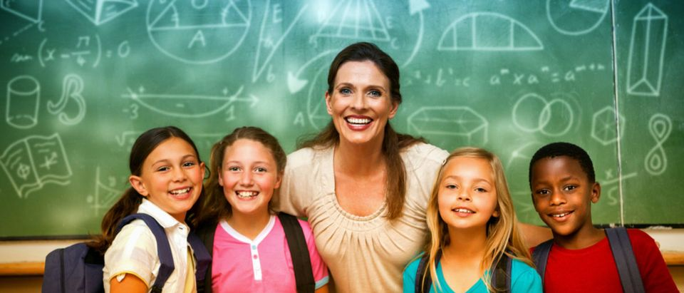 A teacher smiles with her students. (Shutterstock/vectorfusionart)