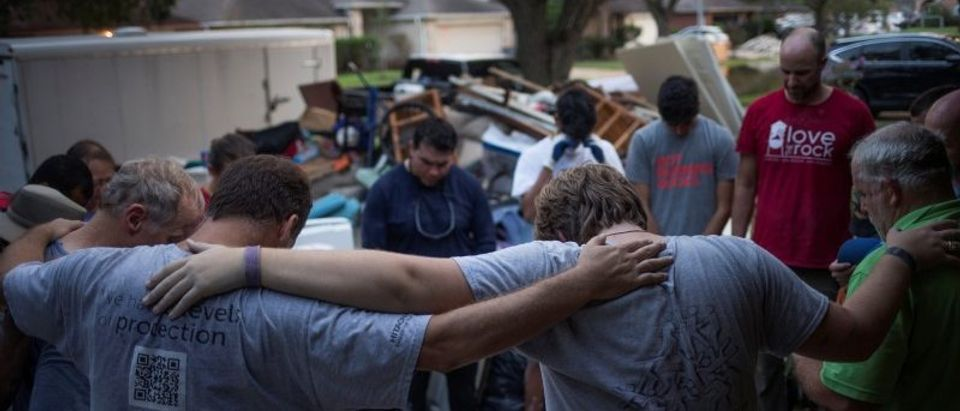 Samaritans pray after helping clear furniture from flooded house of neighbor in aftermath of Tropical Storm Harvey in Houston