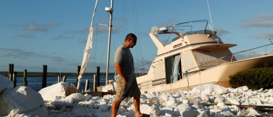 A resident walks past a boat that was pushed onto the shore after Hurricane Irma passed through in St Marys