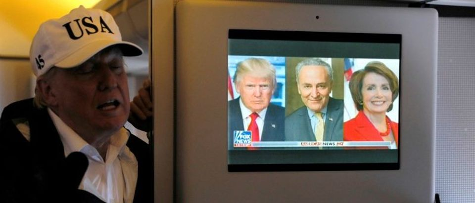 A news report about Trump's relationship with Schumer and Pelosi plays on a television as he speaks to reporters in the press cabin aboard Air Force One