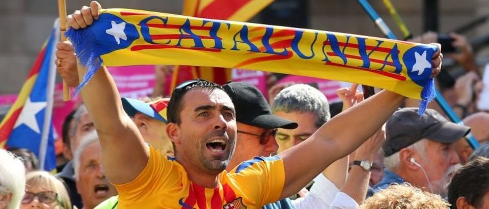 Man raises up a scarf during the Catalans mayors protest in Barcelona