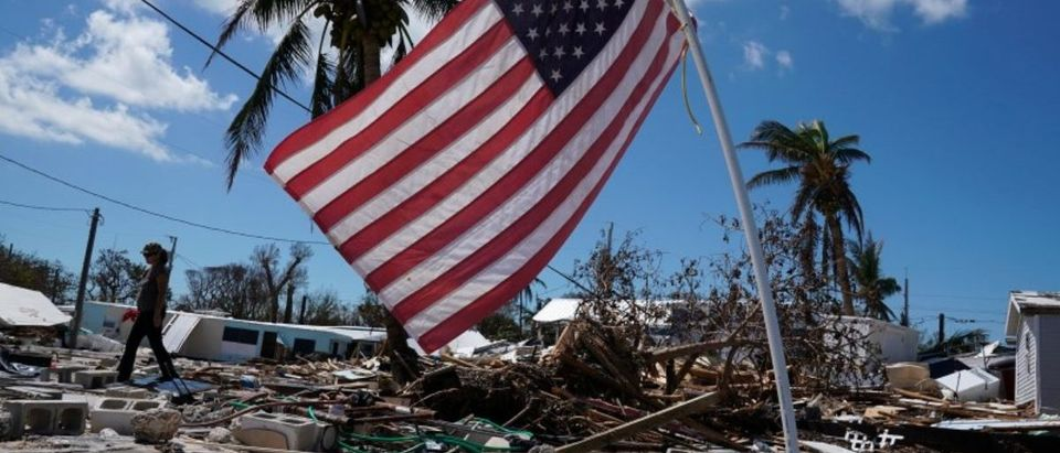 A resident carries belongings next to a U.S. flag in a debris field of former houses following Hurricane Irma in Islamorada