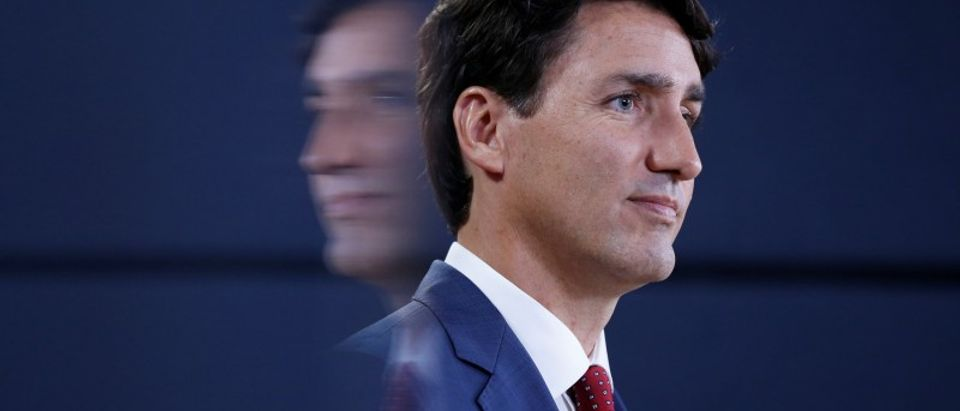 Canada's PM Trudeau is reflected on a screen while taking part in a news conference in Ottawa