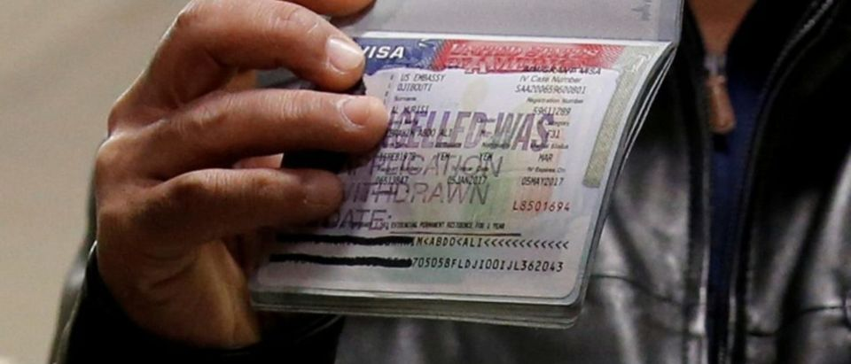 FILE PHOTO: A member of the Al Murisi family, Yemeni nationals who were denied entry into the U.S. because of the travel ban, shows the cancelled visa in their passport from their failed entry to reporters as they successfully arrive to be reunited with their family at Washington Dulles International Airport in Chantilly, Virginia, U.S., February 6, 2017. REUTERS/Jonathan Ernst/Files