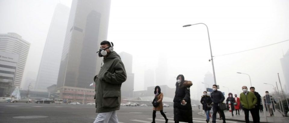 FILE PHOTO: A man wearing a respiratory protection mask walks toward an office building during smog in Beijing