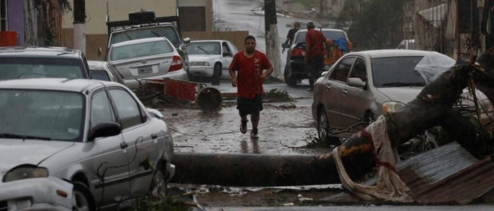 A man runs on the street next to debris and damaged cars after the area was hit by Hurricane Maria in Guayama