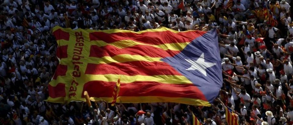 "Catalan pro-independence supporters hold a giant ""estelada"" during a demonstration in Barcelona"