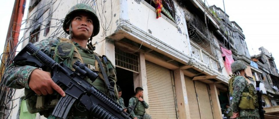 Government soldiers stand guard in front of damaged building and houses in Sultan Omar Dianalan boulevard at Mapandi district in Marawi city
