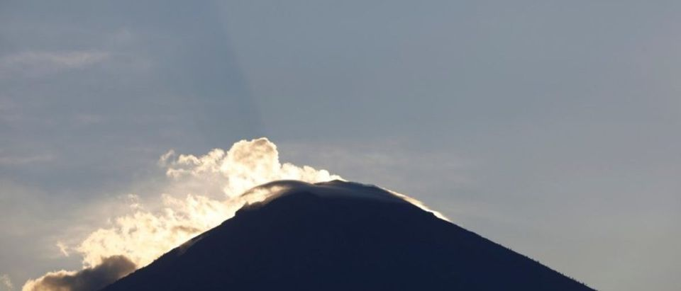 An airliner is seen flying above Mount Agung, a volcano on the highest alert level, from Amed on the resort island of Bali