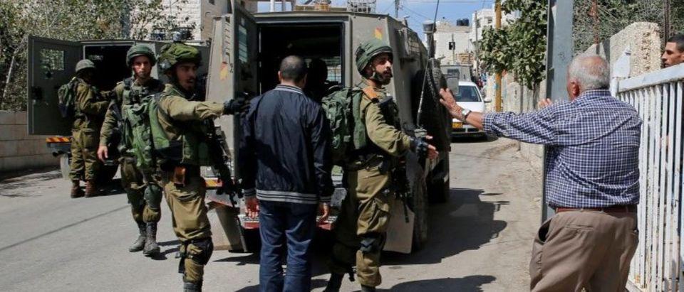 A man argues with Israeli soldiers as they arrest the brother of Palestinian gunman Nimr Jamal near the West Bank City of Ramallah
